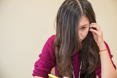 Woman studying. With pen in hand looking angry Stock Photo
