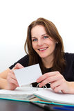 Woman Studying And Smiling. Young Woman Studying and Smiling With A Card in Her Hand Royalty Free Stock Photo