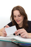 Woman Studying And Smiling. Young Woman Studying and Smiling With A Card in Her Hand Royalty Free Stock Photos