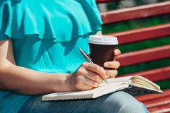 Woman studying and writing in a park Stock Images