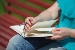 Woman studying and writing in a park Stock Image