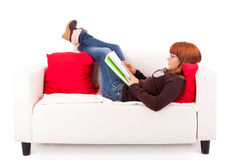 Woman studying. Young happy woman studying on a couch Royalty Free Stock Photos