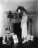 Woman stuffing Christmas stocking Royalty Free Stock Image