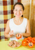Woman stuffing tomato in her kitchen Stock Photos