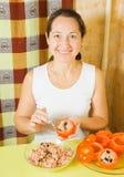 Woman stuffing tomato in her kitchen Stock Photos