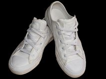White trendy female leather sneakers closeup isolated on the black background. royalty free stock photos