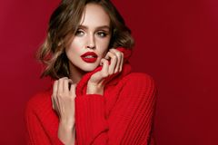 Woman Style. Female Model With Beautiful Makeup And Hairstyle. Portrait Of Young Woman With Bright Make-up And Red Lips In Fashionable Red Clothes On Red royalty free stock photos