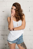 Woman in the style of oldschool and swag looking at the camera. White brick wall, not isolated Royalty Free Stock Image
