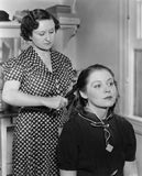 Woman styling another womans hair Royalty Free Stock Photos