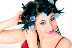Woman styling her hair. Attractive young woman with curlers in her hair stock photography