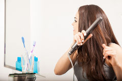 Woman styling her hair in the bathroom Royalty Free Stock Photo