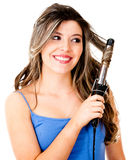 Woman styling her hair with a curler Royalty Free Stock Image