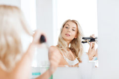 Woman with styling iron doing her hair at bathroom Royalty Free Stock Photography
