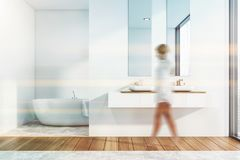 Woman in stylish bathroom interior. Woman walking in modern bathroom interior with white walls, double sink with mirror and comfortable bathtub in background stock image