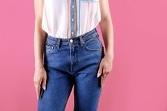 Woman in stylish blue jeans. On color background stock photography