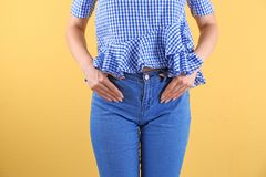 Woman in stylish blue jeans. On color background royalty free stock images