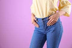 Woman in stylish blue jeans. On color background royalty free stock photography