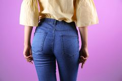 Woman in stylish blue jeans. On color background stock image