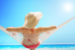 Woman with a stylish hat lying on a hammock. Rear view of a woman in a red swimsuit with a stylish hat lying on a hammock on a beach by the sea royalty free stock images