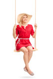 Woman with a stylish hat swinging on a swing Stock Photography