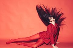 Woman with stylish makeup and long hair posing in total red outfit. Fashion concept. Girl on mysterious face in red stock photos