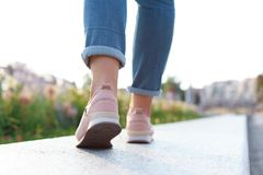 Woman in stylish sneakers walking outdoors Stock Photo