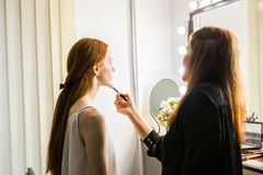 Woman stylist doing makeup beautiful girl in beauty salon Royalty Free Stock Photography
