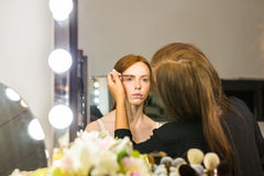 Woman stylist doing makeup beautiful girl in beauty salon Stock Images