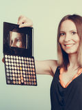 Woman stylist holding eyeshadow makeup palette. Royalty Free Stock Photo