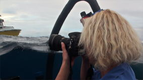 Woman on submarine on rwater photographs yacht in Pacific Ocean. stock footage
