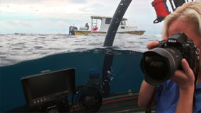 Woman on submarine underwater photographs yacht in Pacific Ocean. stock video