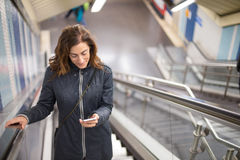 Woman in subway mechanic stairs reading phone Royalty Free Stock Image
