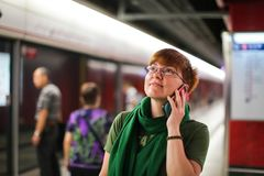 Woman on subway metro commute public transport station talking on phone while walking to arriving train.  stock image