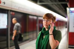 Woman on subway metro commute public transport station talking on phone while walking to arriving train.  stock images