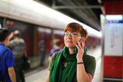 Woman on subway metro commute public transport station talking on phone while walking to arriving train.  stock photos