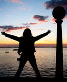 Woman success. Woman silhouette against sunset background in the lake Stock Images
