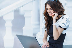 The woman, a successful businessman working on laptop. Cute business woman brunette with long curly hair,dressed in a black dress with white sleeves,sitting on royalty free stock image