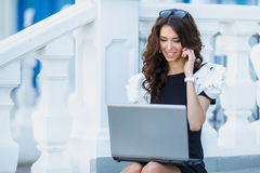 The woman, a successful businessman working on laptop. Cute business woman brunette with long curly hair,dressed in a black dress with white sleeves,sitting on royalty free stock images