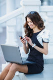 The woman, a successful businessman working on laptop. Cute business woman brunette with long curly hair,dressed in a black dress with white sleeves,sitting on royalty free stock photography