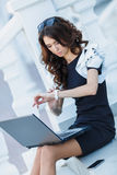 The woman, a successful businessman working on laptop. Cute business woman brunette with long curly hair,dressed in a black dress with white sleeves,sitting on stock photo