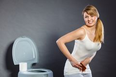 Woman suffer from belly pain holds pills in toilet Stock Image