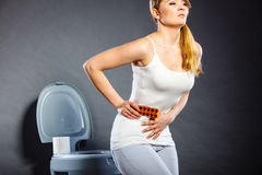 Woman suffer from belly pain holds pills in toilet Royalty Free Stock Photography