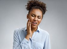 Woman suffering from annoying strong teeth pain. Photo of african american woman in blue shirt on gray background. Medical concept stock photo