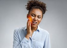 Woman suffering from annoying strong teeth pain. Photo of african american woman in blue shirt on gray background. Medical concept stock images
