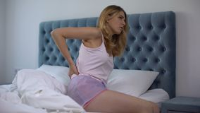 Woman suffering back pain sitting in bed, uncomfortable mattress, nerve problems. Stock footage stock video footage