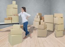 Woman suffering from backache while moving boxes stock photo