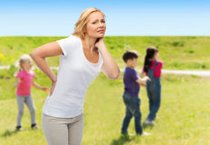 Woman suffering from backache over group of kids Royalty Free Stock Image