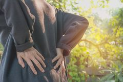 A woman suffering from backache, spinal injury and muscle issue. Problem at outdoor Royalty Free Stock Photo