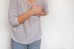 A woman suffering from chest pain. Health problem. Woman holding hands on the breast royalty free stock photography