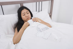 Woman suffering from cold having coffee in bed Stock Photography